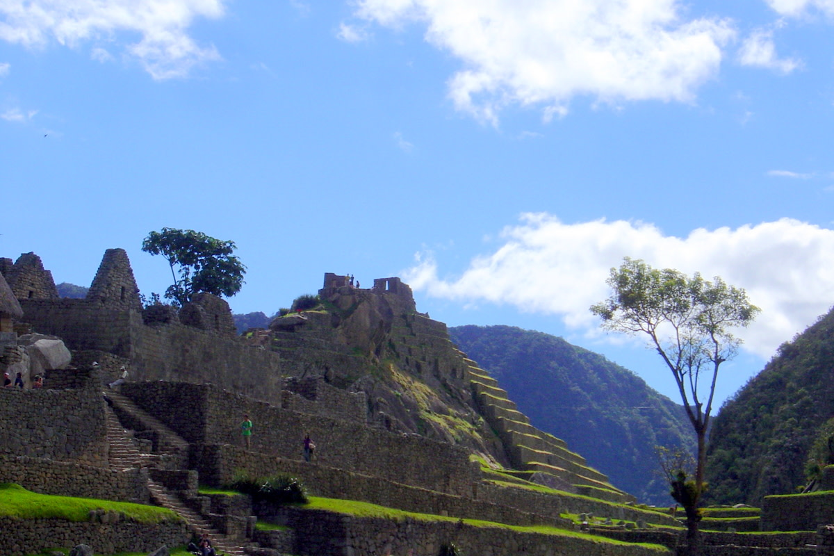 Terraced ruins being explored by a few tourists, with trees framing the brilliant sky.