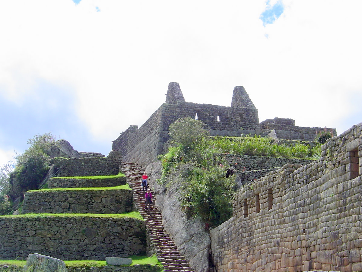 Travelers enjoy descending the stone steps along walls, all constructed by Incas prior to 1500 A.D., with the vivid grass and shrubbery adding green to the surroundings.