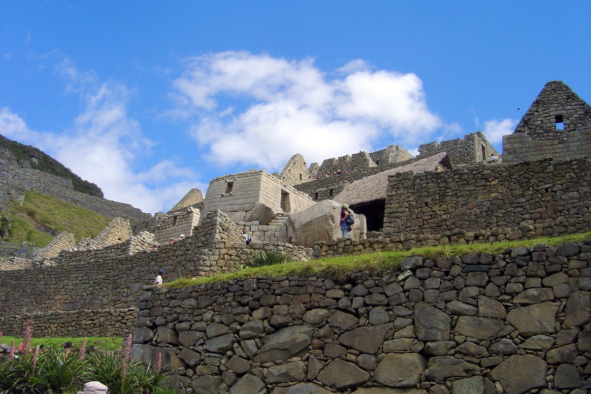 Looking upward past the masterfully constructed stone walls of Machu Picchu to the brilliant blue sky adorned by a few clouds.
