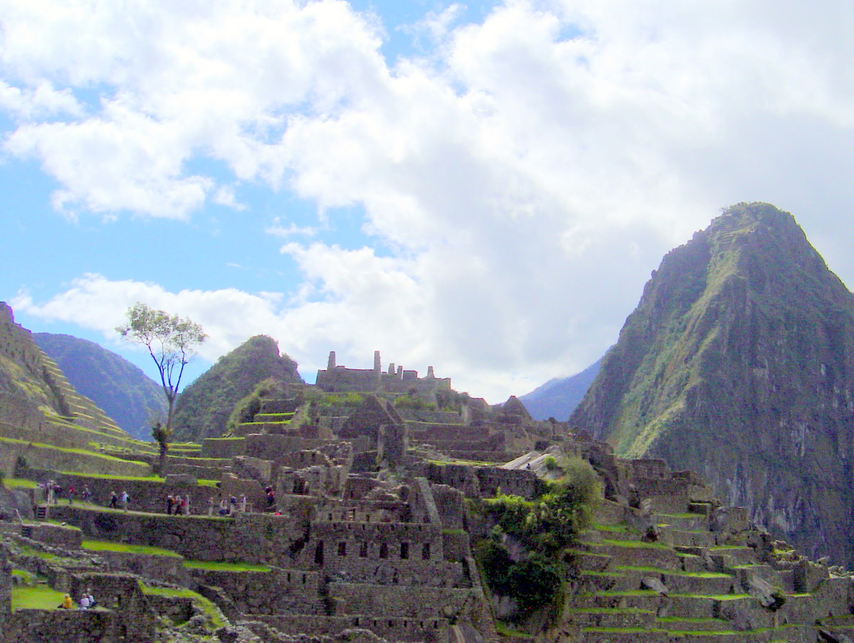 A side view of Machu Picchu with tourists walking along the terraces and rock walls; the scene is enhanced by the stunning sky.