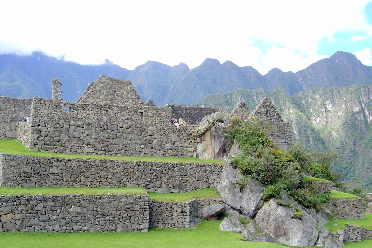 View of a young couple relaxing and enjoying the serenity of Machu Picchu's walls and terraces after a day of touring. The Andes are in the background.
