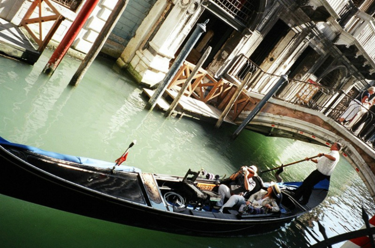 A gondola with a touring couple being poled through a canal under a bridge