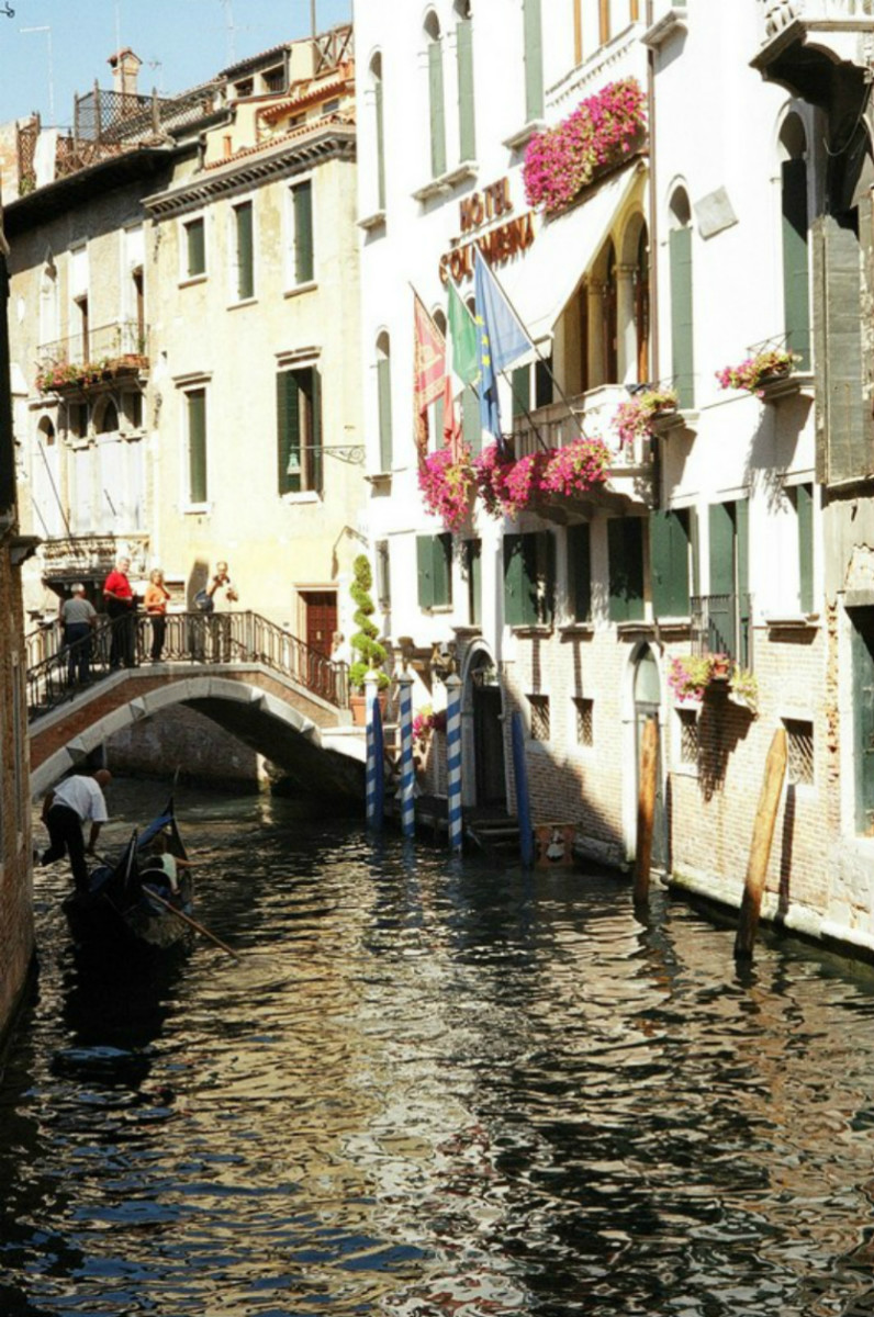 Flowers and flags adorn a hotel overlooking a bridge over a small canal, with a gondola passing through.