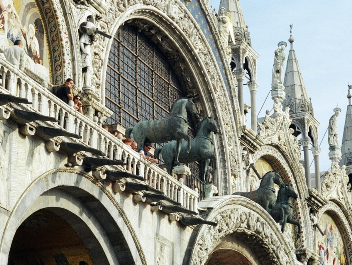 A close-up of the archways of the ornate facade of St. Mark's Basilica, with the replicas of the ancient bronze horses on the balcony, accompanied by tourists. The original horses were placed inside the Basilica to protect them from the weather.