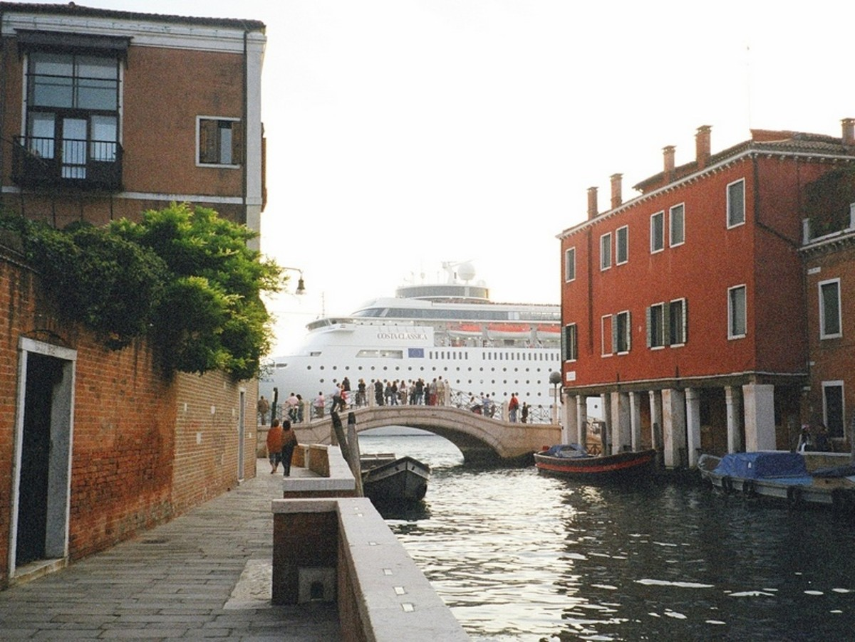 A large cruise ship passes, dominating the view, as tourists look on from a bridge over a canal in Venice.