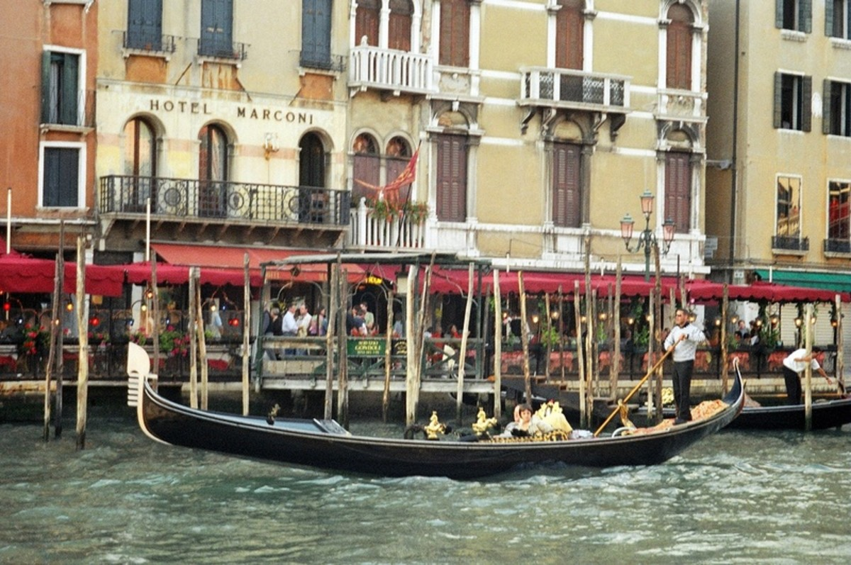 An elegant, classic gondola being propelled through the Grand Canal in front of the Hotel Marconi in central Venice.
