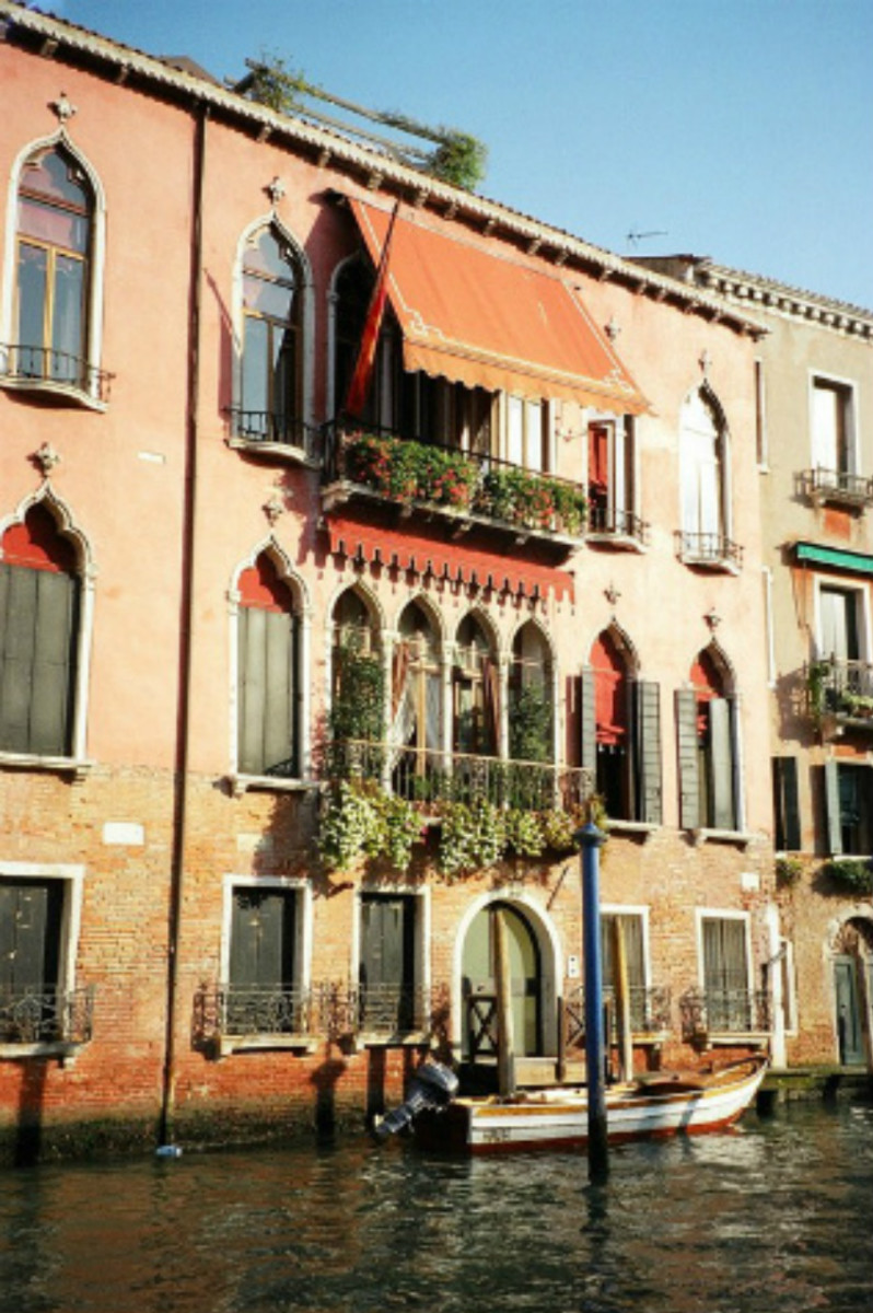 A beautiful home with Moorish architecture and vivid colors on a canal in Venice. Its small motor boat waits at the doorstep to provide transportation for its owners.