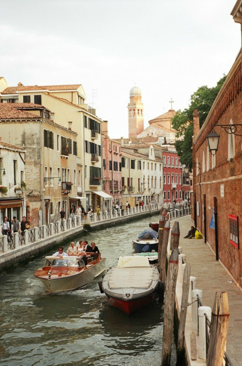 A water taxi in the mode of a classic speedboat carries a wedding party down a canal in Venice, flanked by walkways of sightseers celebrating the beauty of this unique city, where, instead of streets, there are only waterways.