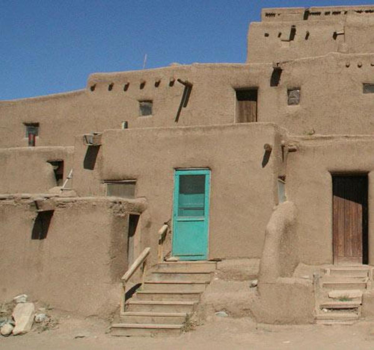 Taos pueblo with blue door similar to Henrietta's pueblo.