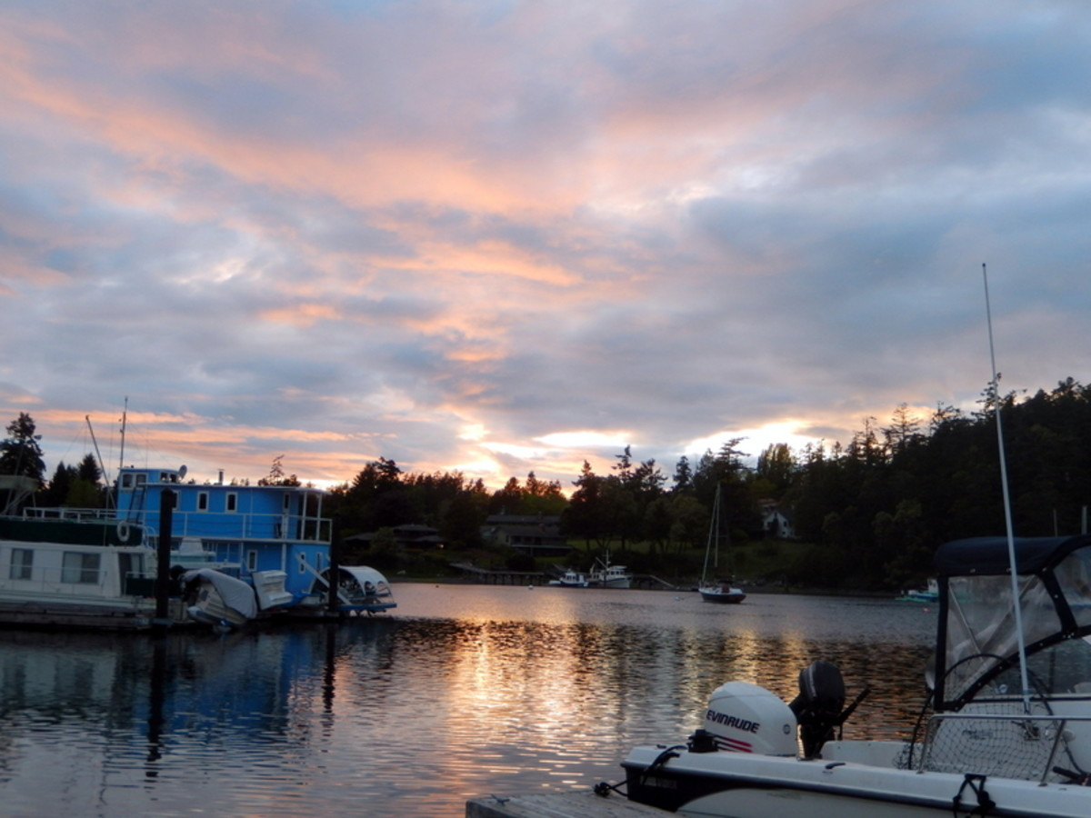 Striking colors cloak a small, tranquil side bay cradling a few small houseboats and fishing boats as the forest ashore welcomes the setting sun.