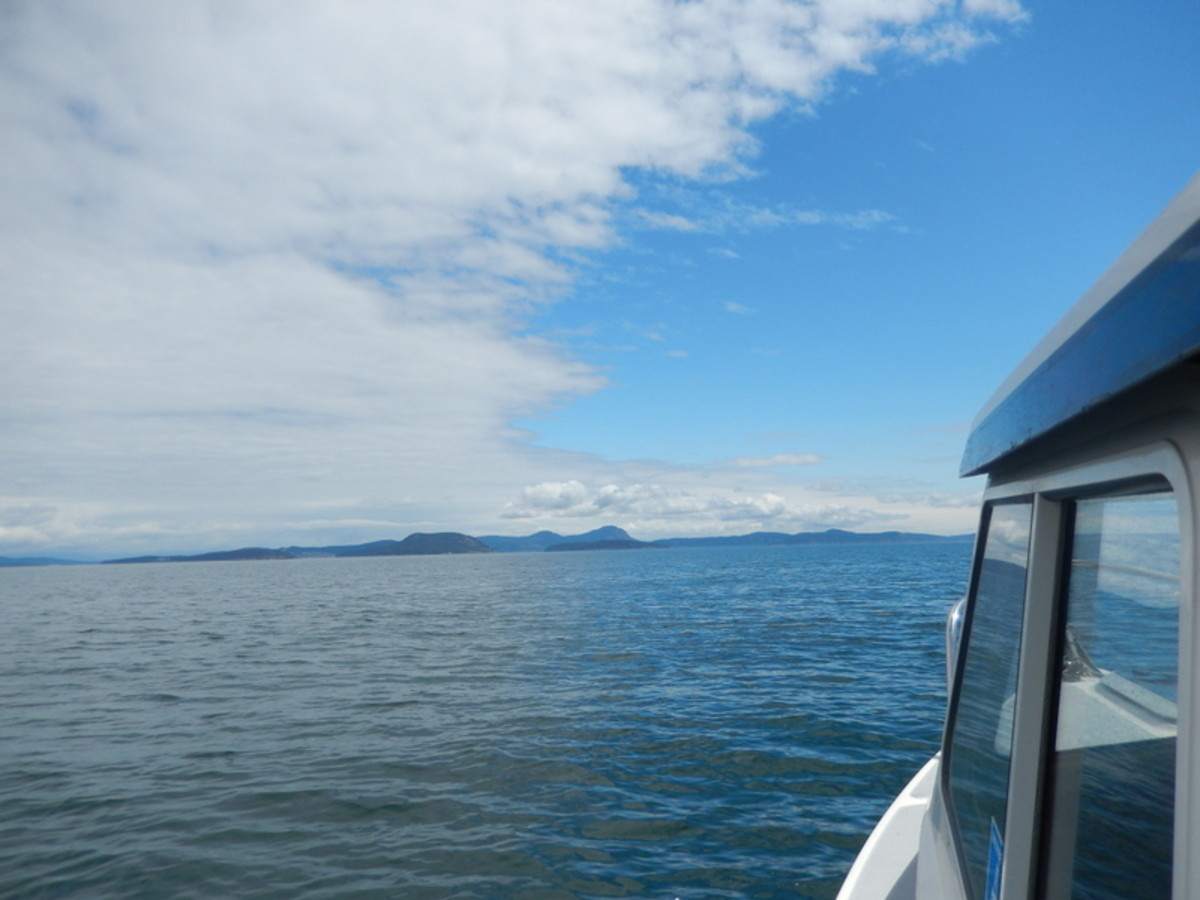 View across Rosaio Strait from a small cruiser heading toward islands and on to Friday Harbor. Notice how thespectacular sky--half cloudy and half blue--is reflected in the sea.