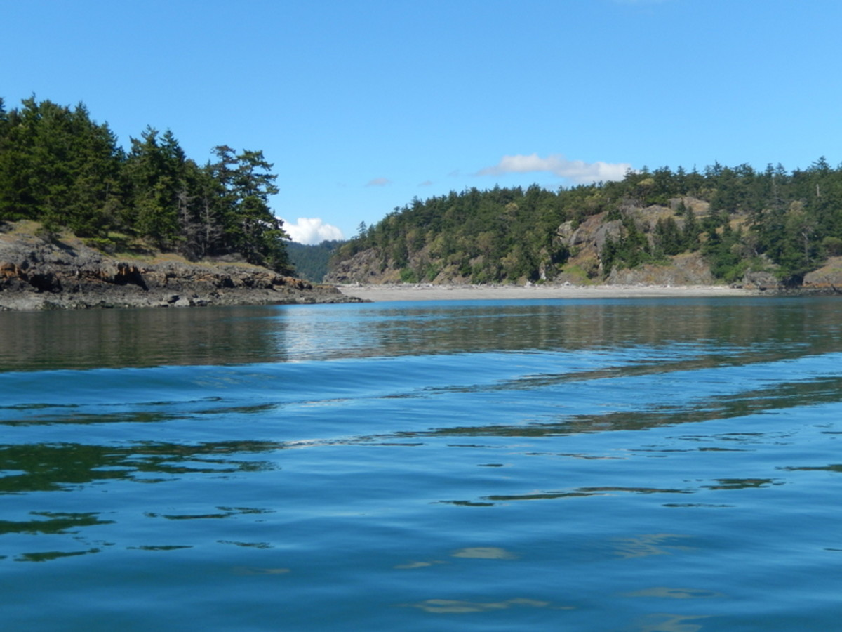 The view between two charming tree-covered islands in the San Juans, with an inviting beach on one side.