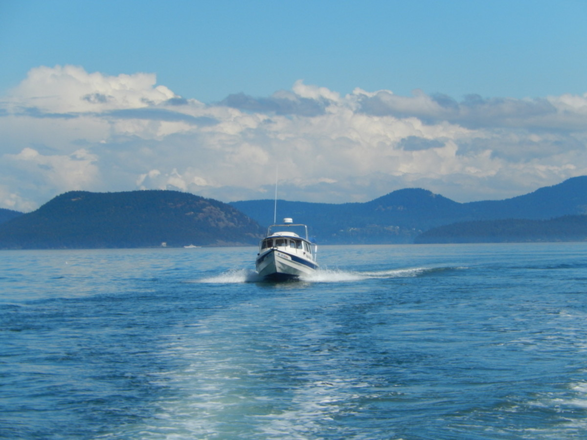 A C-Dory, a small pocket cruiser, crossing Rosario Strait, with some of the San Juan Islands in the background.