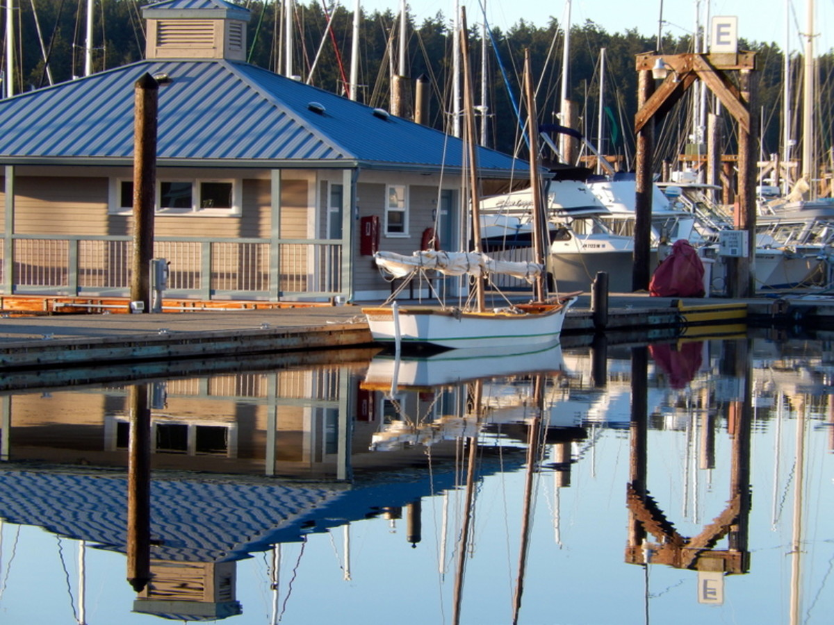 A modern restroom building with showers at the Friday Harbor Marina, with a classic sailing vessel reflected in the water alongside.