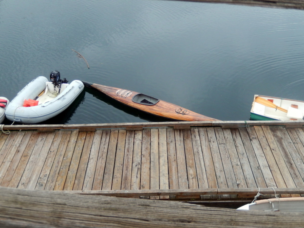 Several types of dinghies were parked at a dock in the marina. They were used to paddle out to anchored boats.One was an attractive, handmade wooden kayak.