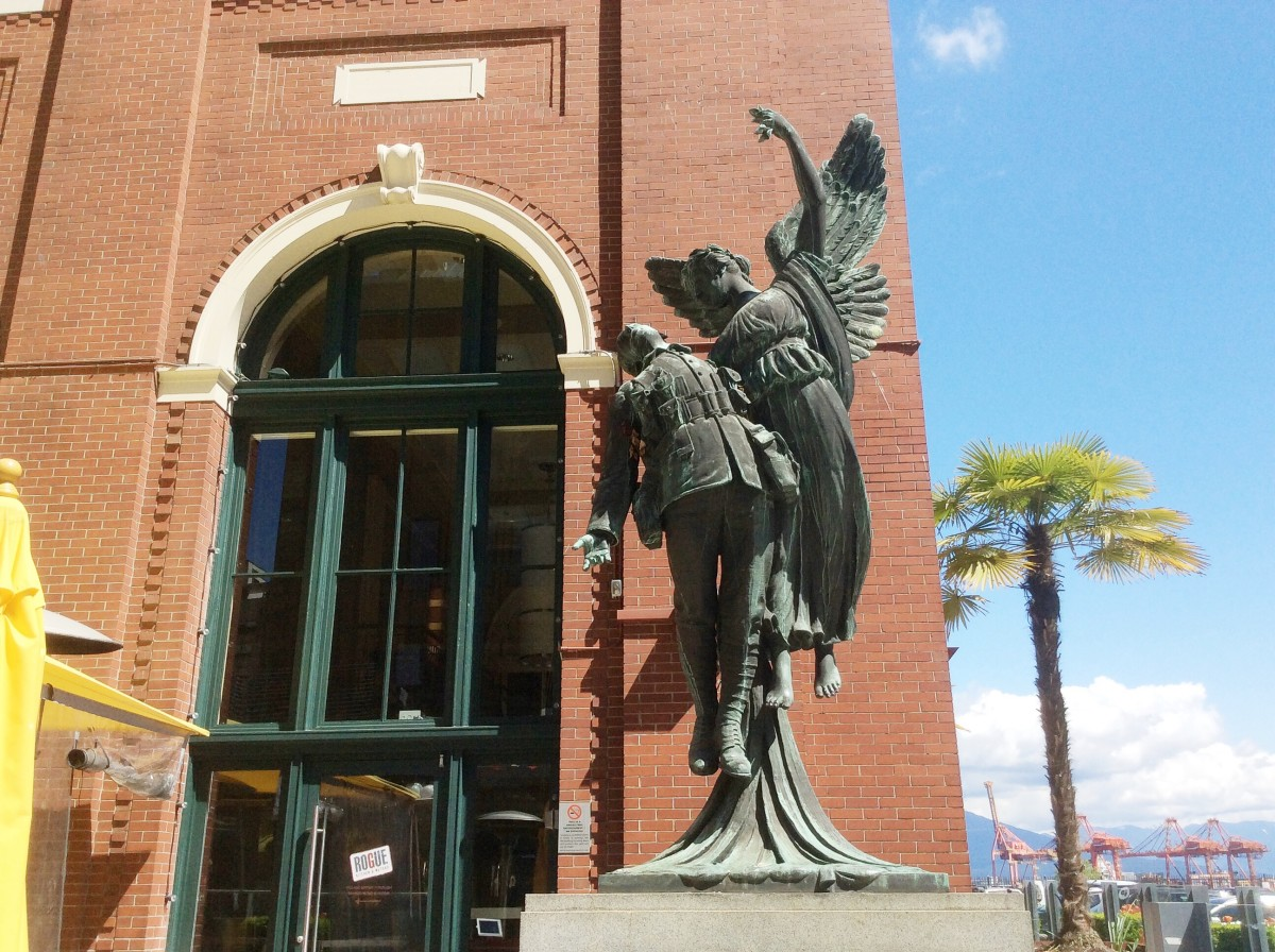 A view of the sculpture that shows the angel's raised hand and the missing wreath