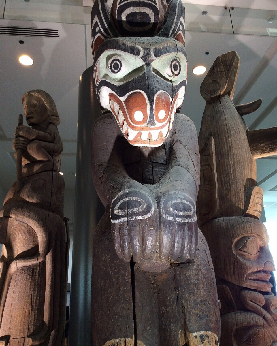 This is a close-up view of the three totem poles in the Vancouver Convention Centre. The middle pole is very tall and extends to the second storey of the building.