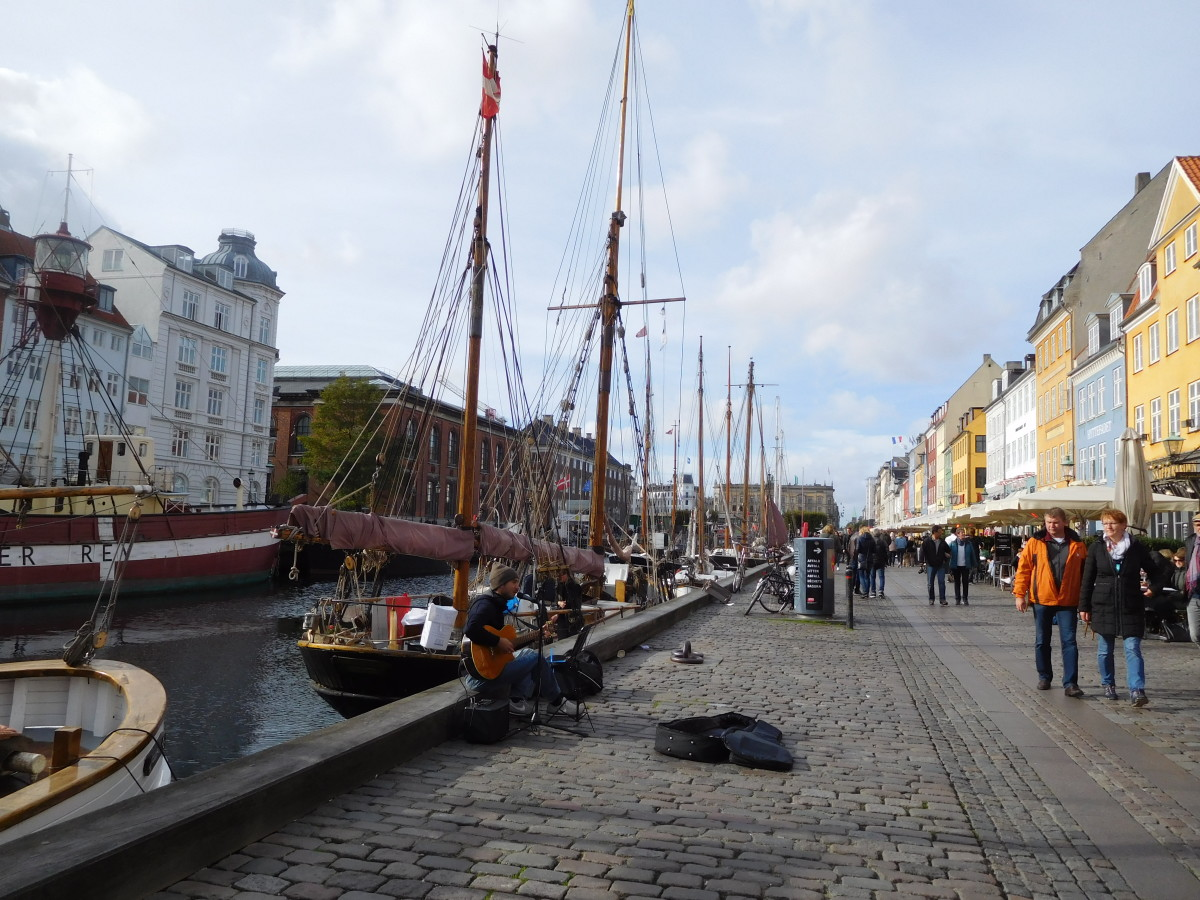 Diners at outside cafes being entertained by a guitarist in Nyhavn Harbor in Copenhagen.