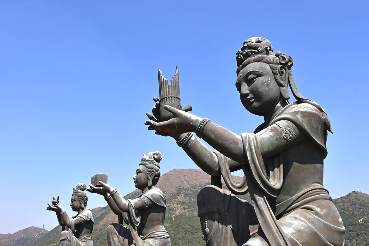 Beside the Buddha are six Deva statues. Each holds a different offering for the Enlightened One.