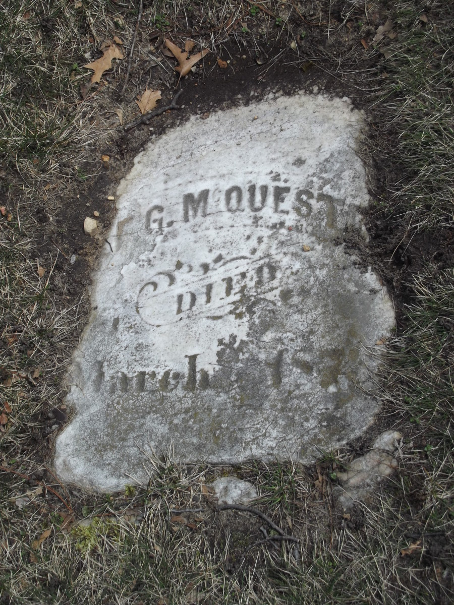 A somewhat square tombstone flat on the ground that is mostly intact.  The text is relatively faded.  The grass has grown over the sides.  Evergreen Cemetery, Muskegon, MI.