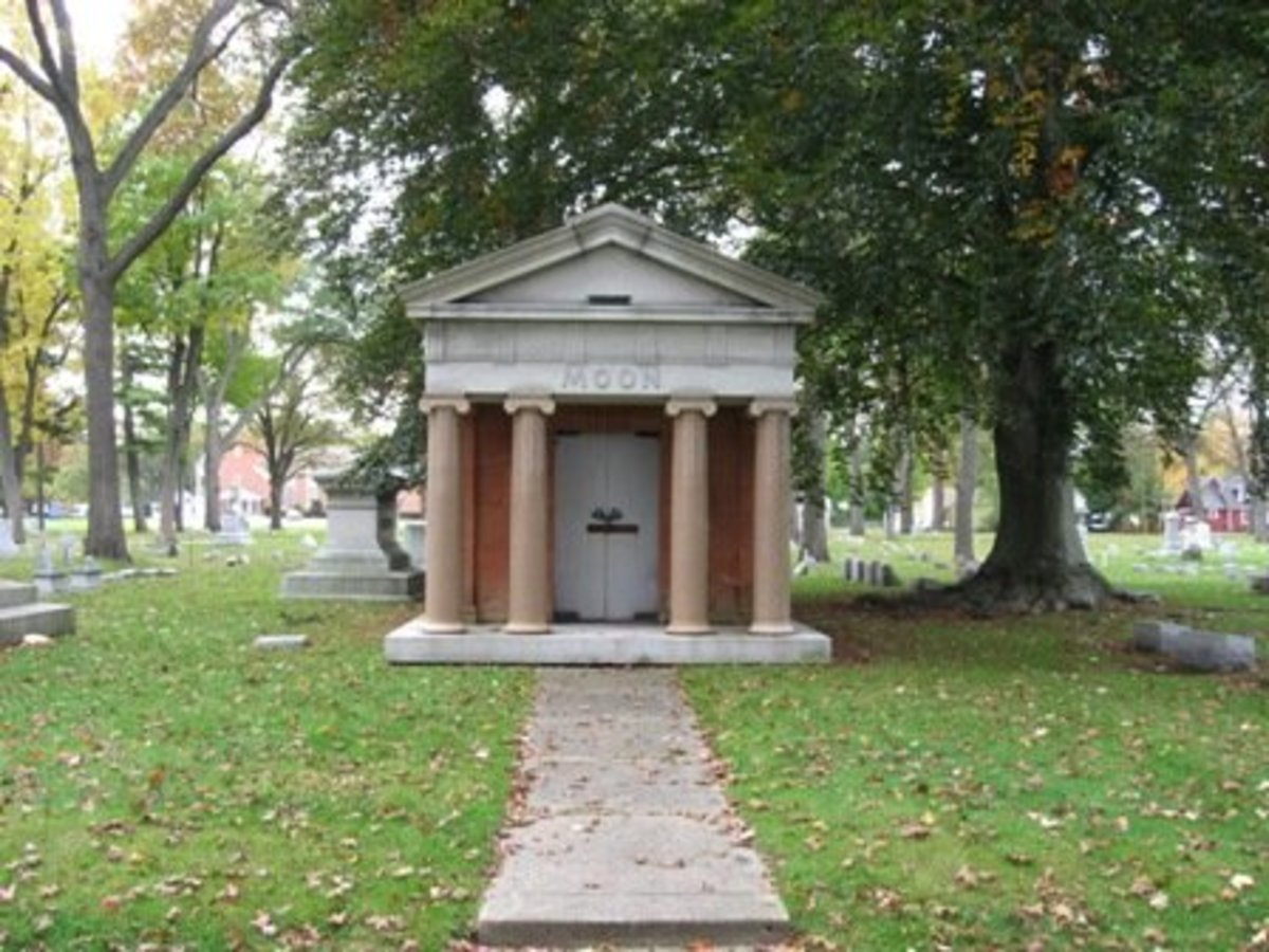 Image of mausoleum with columns out front and grey granite doors.  Mausoleum itself is sandstone colored with columns of matching terracotta granite.  Moon family crypt, Evergreen Cemetery, Muskegon, MI.