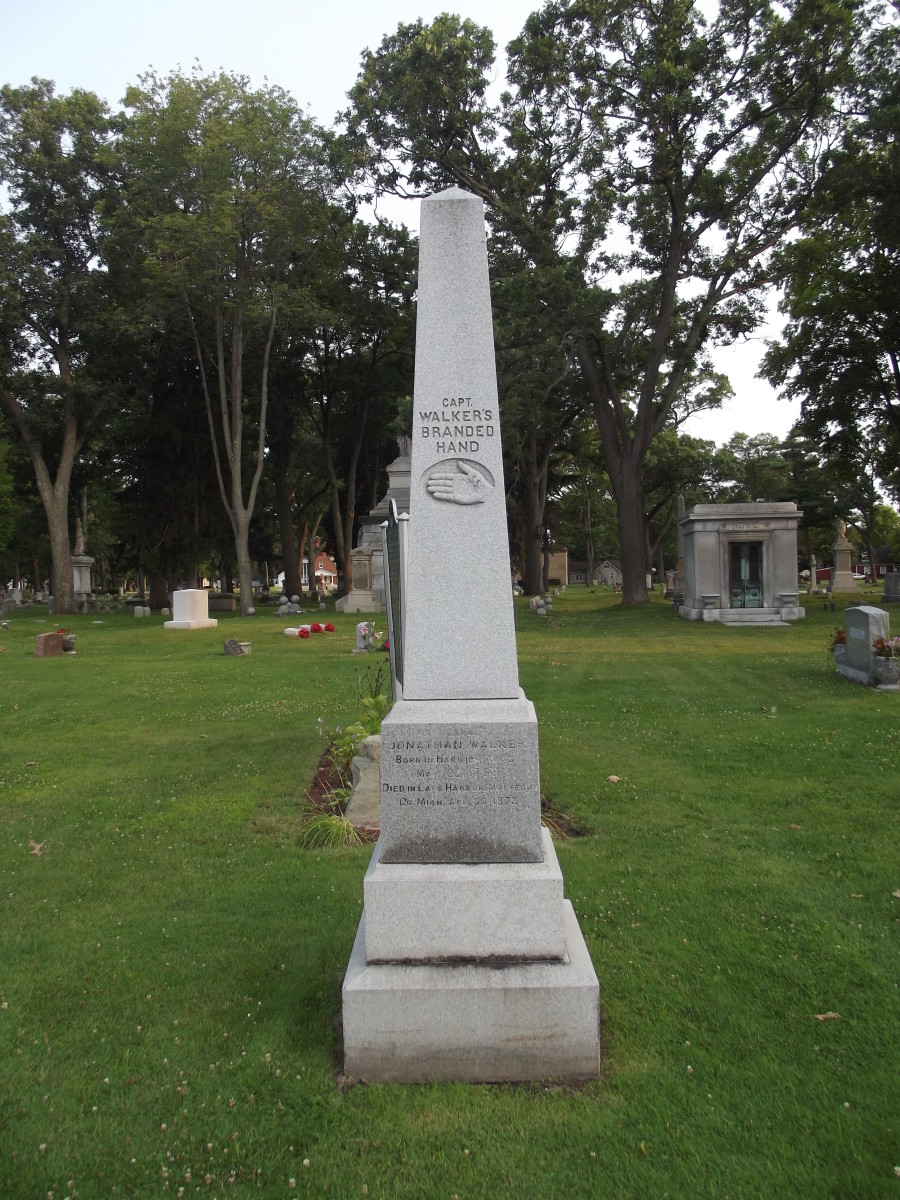 "Obelisk grave marker of Captain Jonathan Walker.  Monument is marked with an engraved relief of a man's hand branded with SS and the text ""Captain Walker's Branded Hand.""  Evergreen Cemetery, Muskegon, MI."