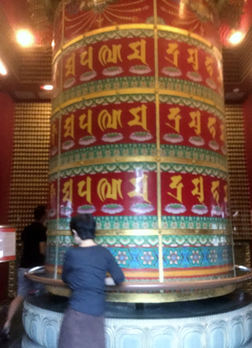 The prayer wheel in the rooftop garden of the Buddha Tooth Relic Temple, Singapore. According to the Buddhist tradition spinning  a prayer wheel will have much the same meritorious effect as orally reciting the prayers.