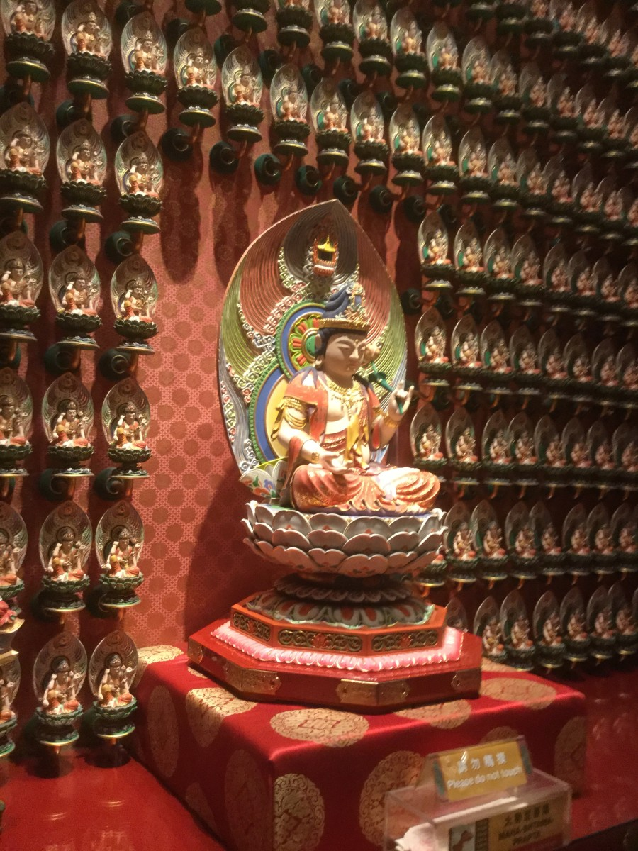 One hundred Buddha statues line this wall on the first floor of the Buddha Tooth Relic Temple. Each individual statue has a name and a specific hand sign, called a mudra.