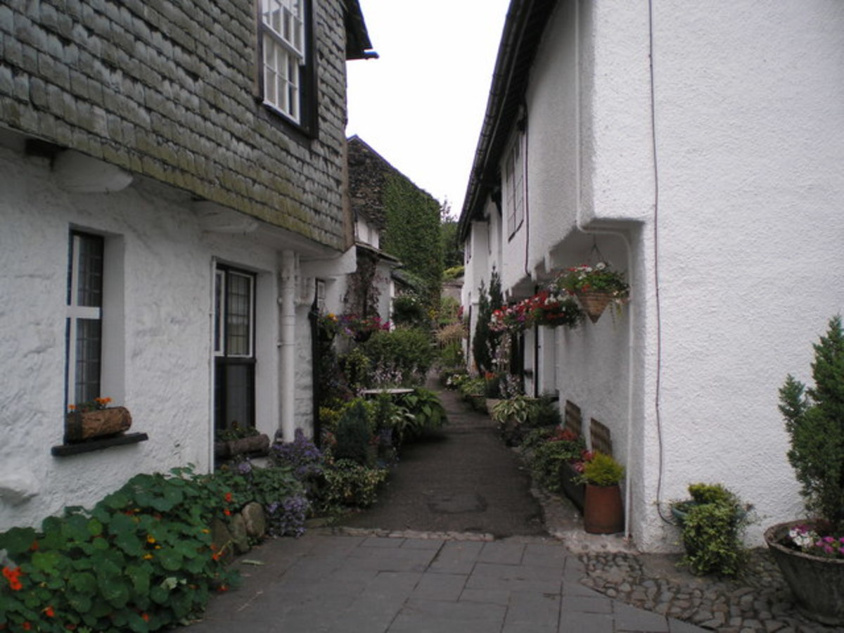 Narrow Lane in Hawkshead Village with pots and hanging baskets in bloom