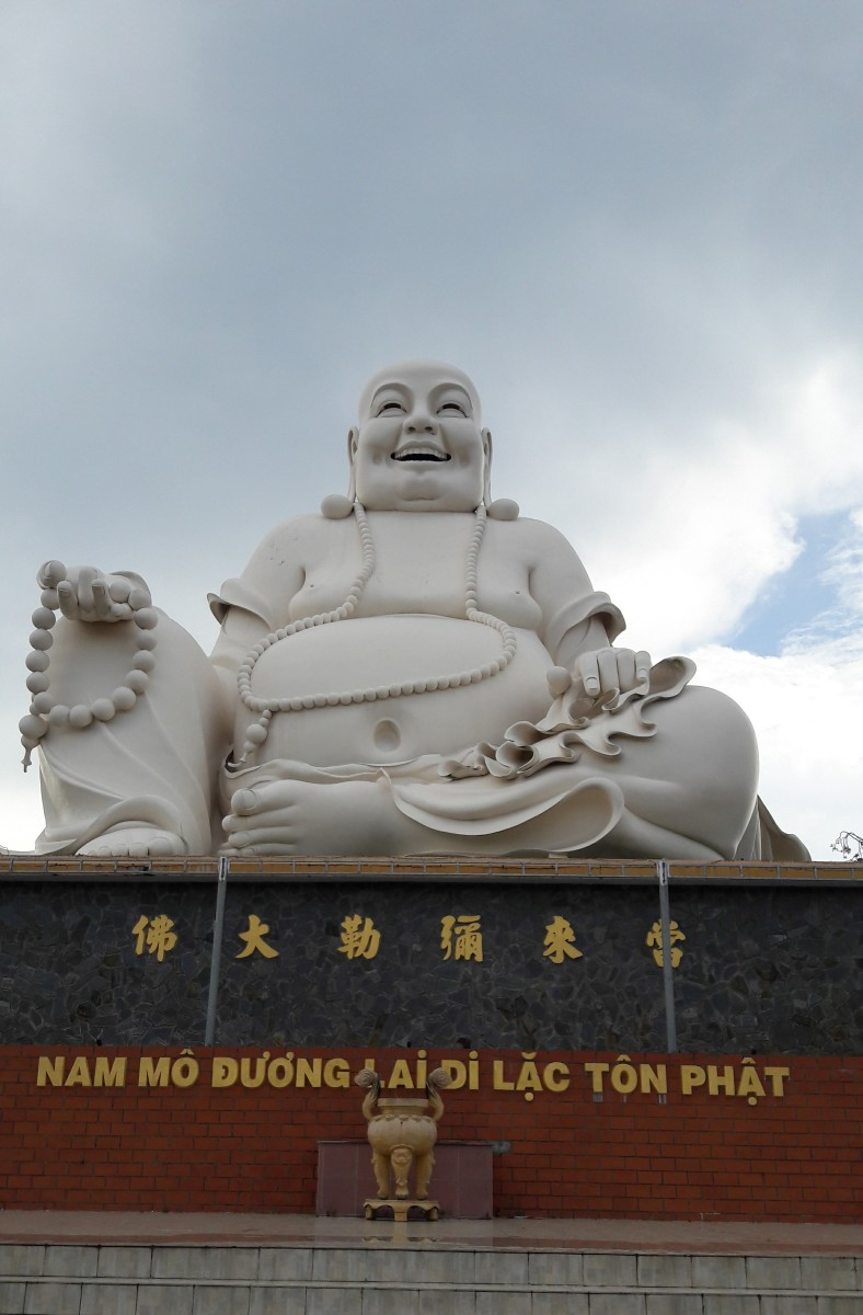 Budai statue sits humbly outside in the pagoda.