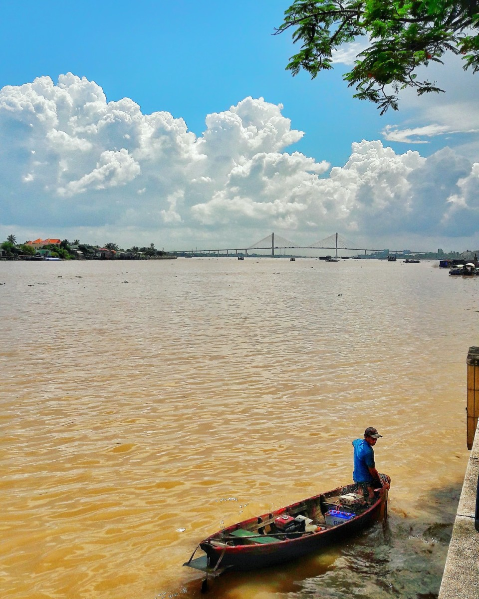 A local man is fishing with the Rach Mieu Bridge in the backdrop.