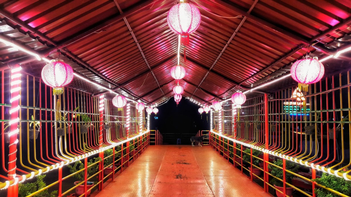 The boat dock is lighted with lanterns lending a sense of the past with Chinese influence.