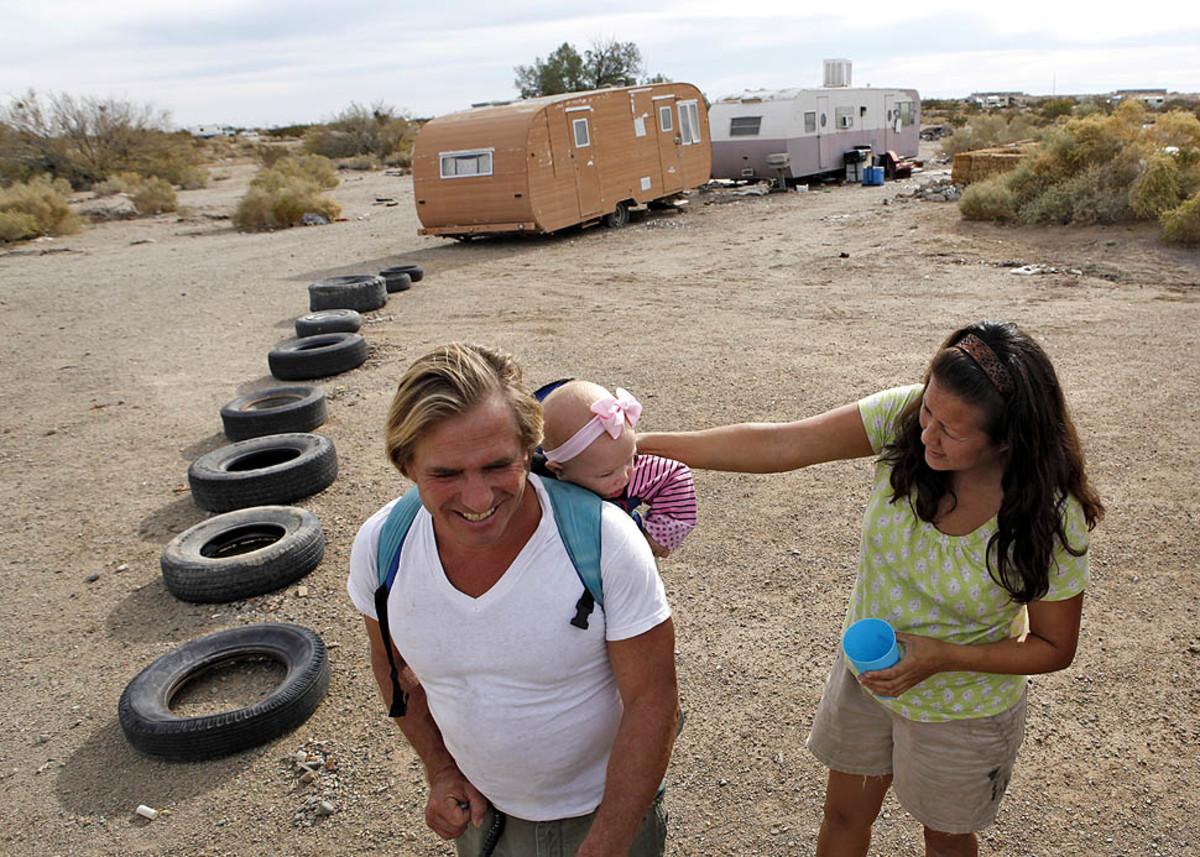 A couple with their 10-month-old daughter outside their trailer in Slab City.