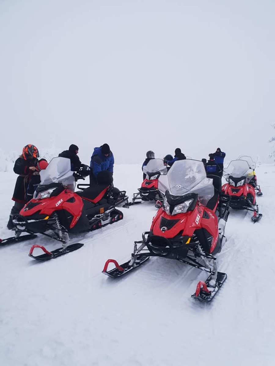 Dismounting the snowmobiles on the hilltop.