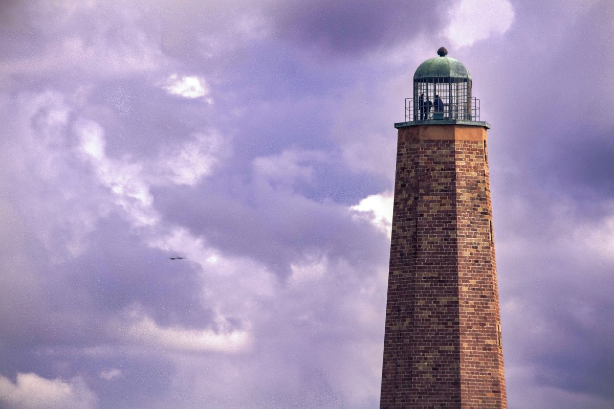 Old Cape Henry Lighthouse with 2 F-18s passing by in the distance from NAS Oceana.