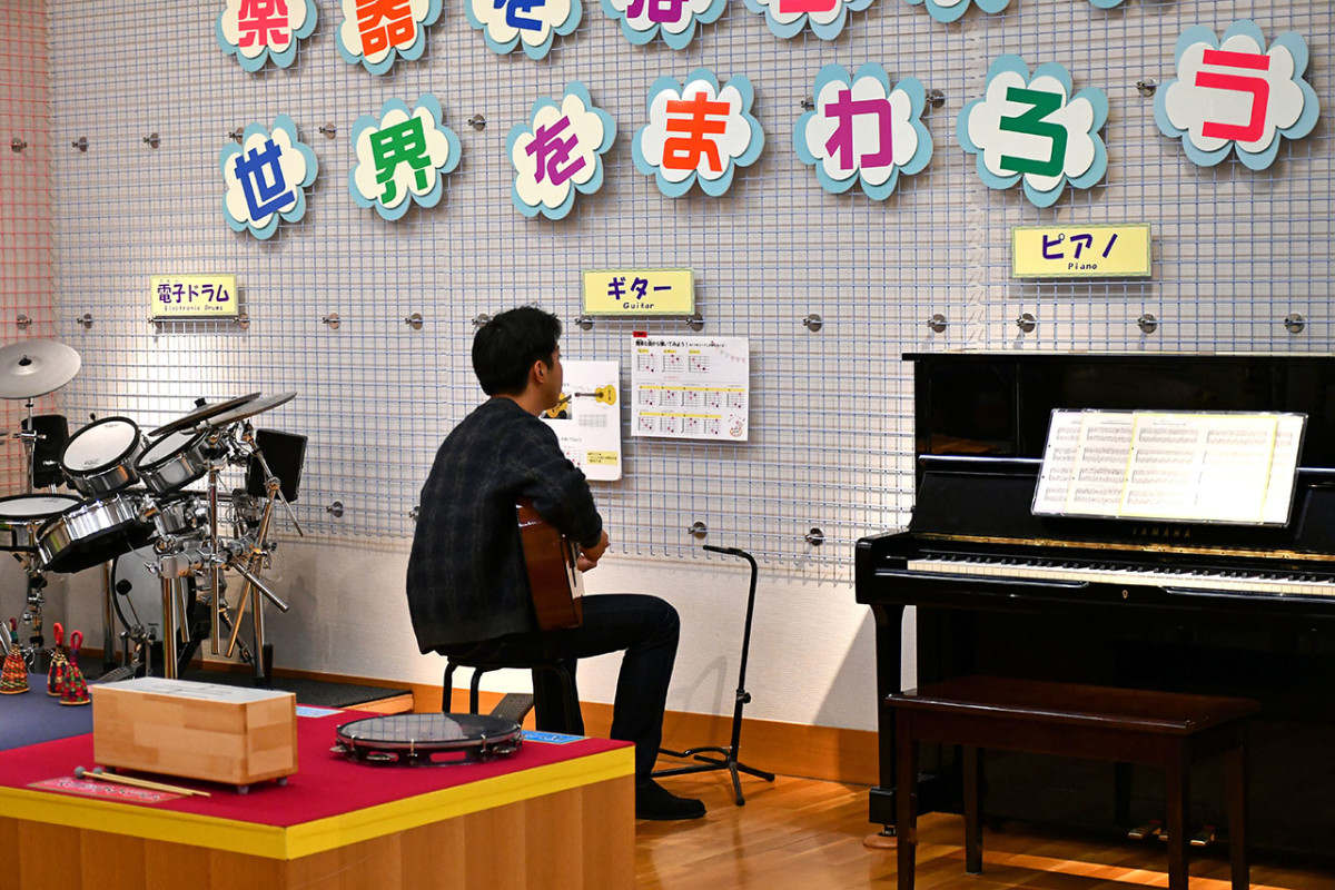 A Japanese visitor experimenting with Nylon Guitar licks in the Hands-on Room.