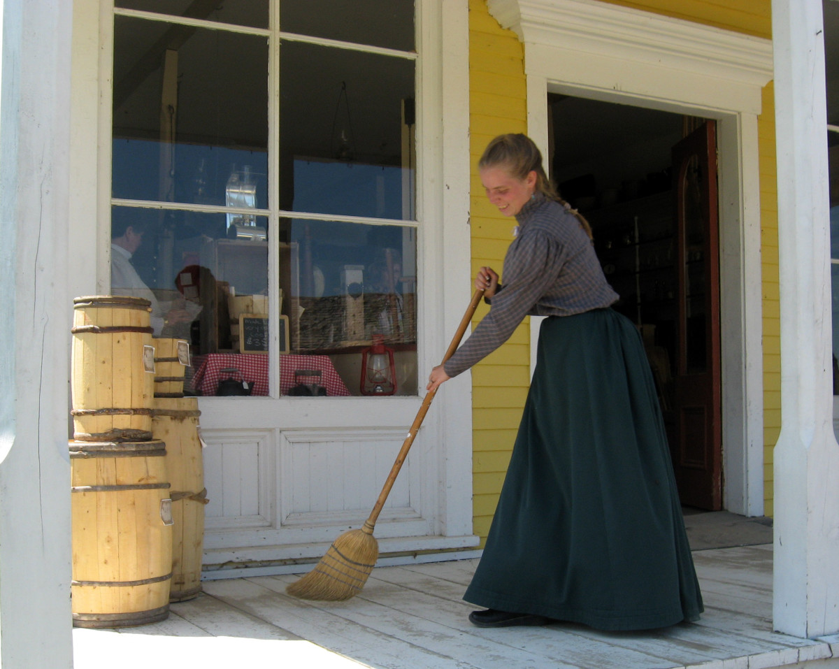 Sweeping the porch of the general store.