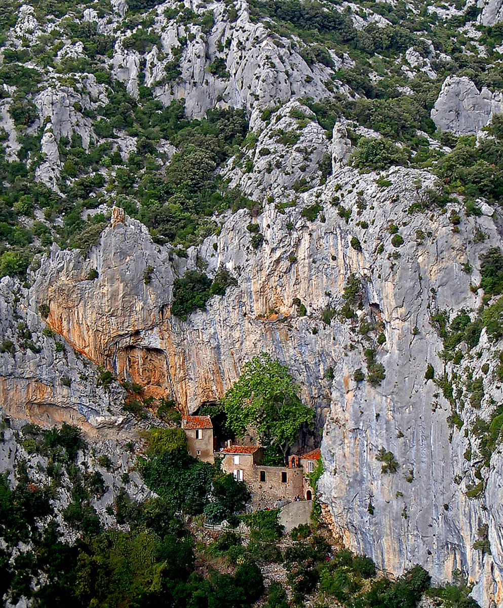 "Ermitage de Galamus perches on a vertical rock cliff.  ""Ermitage"" means hermitage which is related to hermit - someone who retreats from society to live in solitude, often for religious reasons."