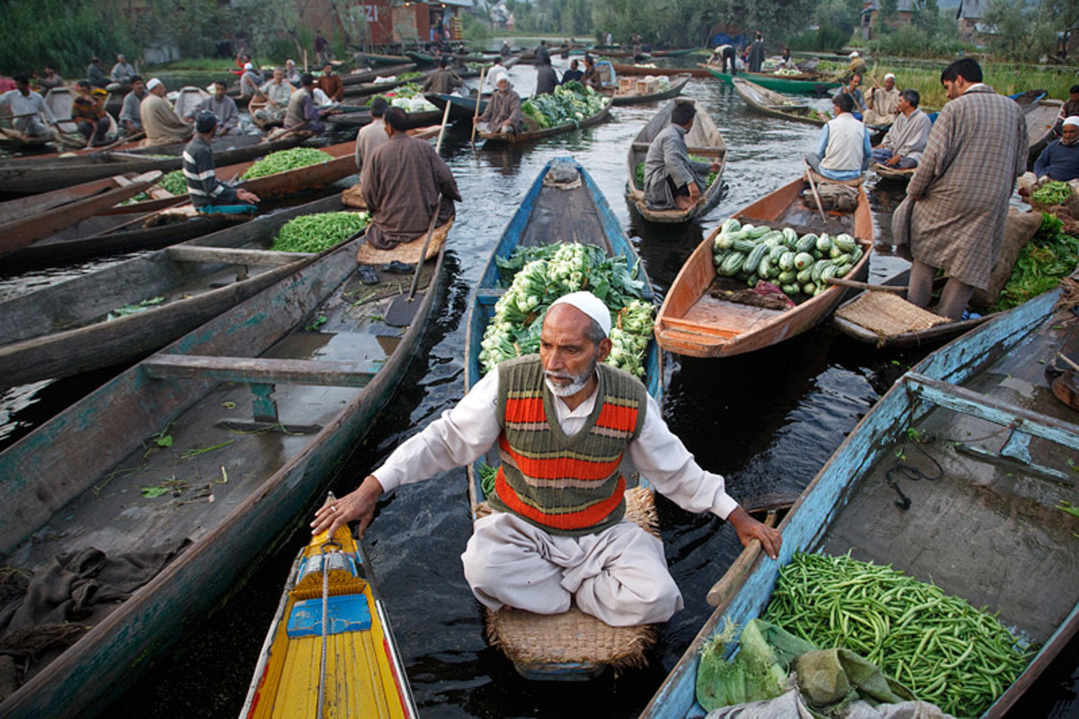 Vegetable seller sitting in front of the canoes with cross-legged position.