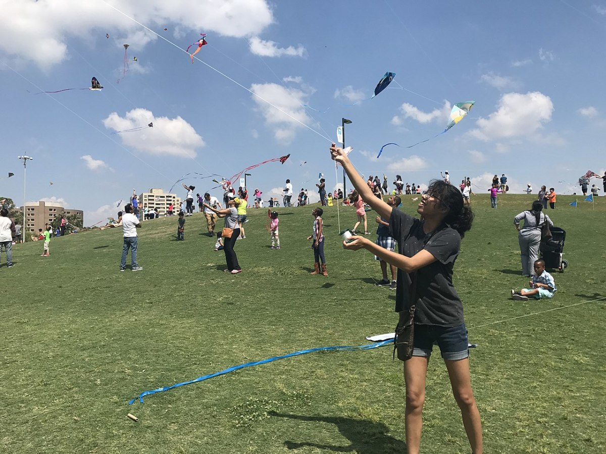 People flying kites on the hill near Miller Outdoor Theater