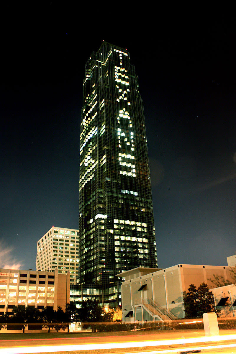 Williams Tower lit up at night showing the word TEXANS