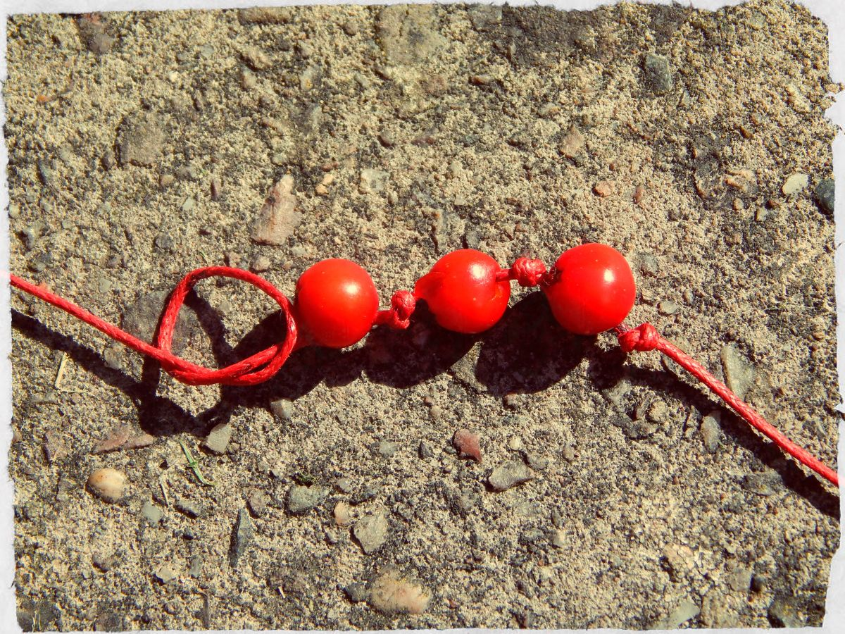 Tie a knot between each berry to secure it into place.