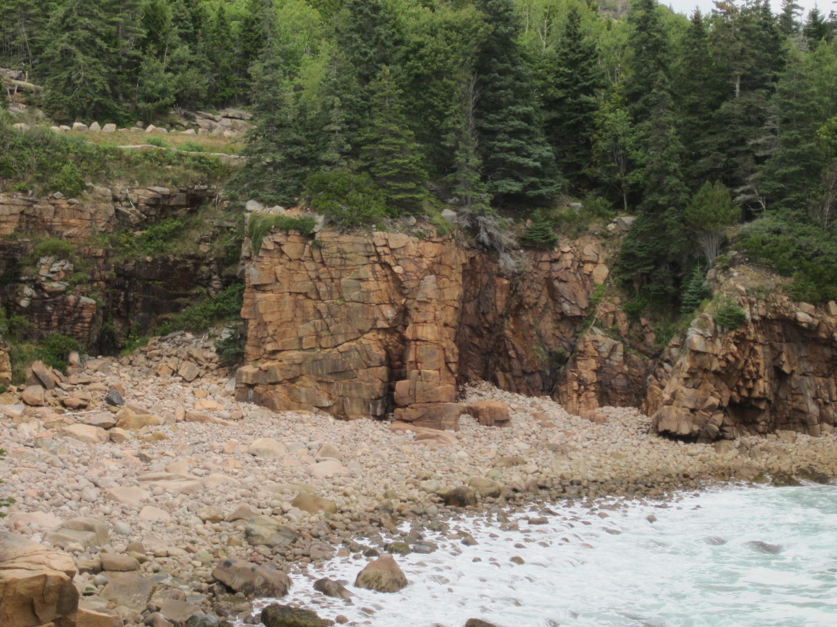 A 20 foot pillar of rock stands in front of the shear granite shore in Monument Cove