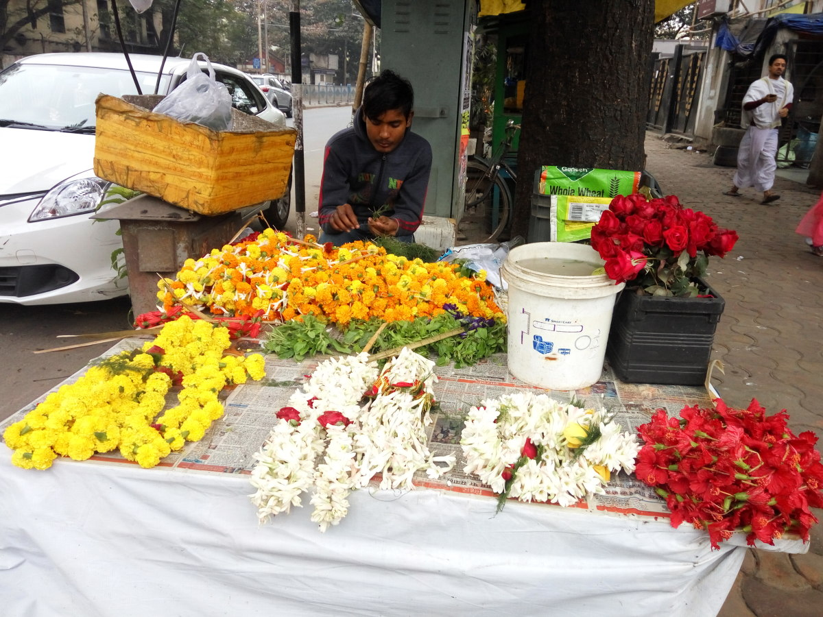 A vendor in Kalighat selling a variety of different flowers.