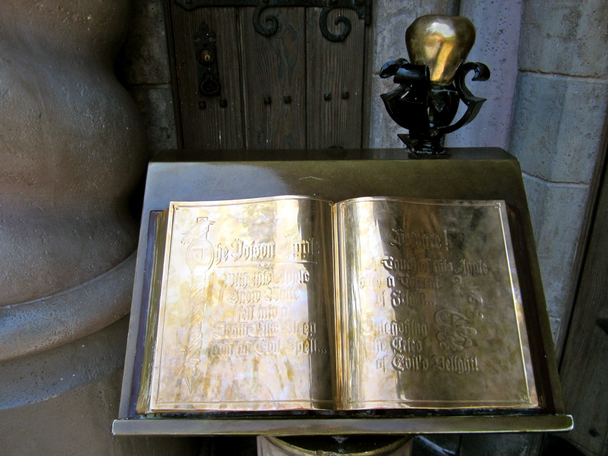 The spell book and brass apple outside of Snow White's Scary Adventure.