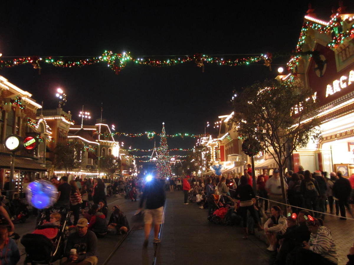 Main Street USA decorated for the holidays with a giant Christmas tree at the end.