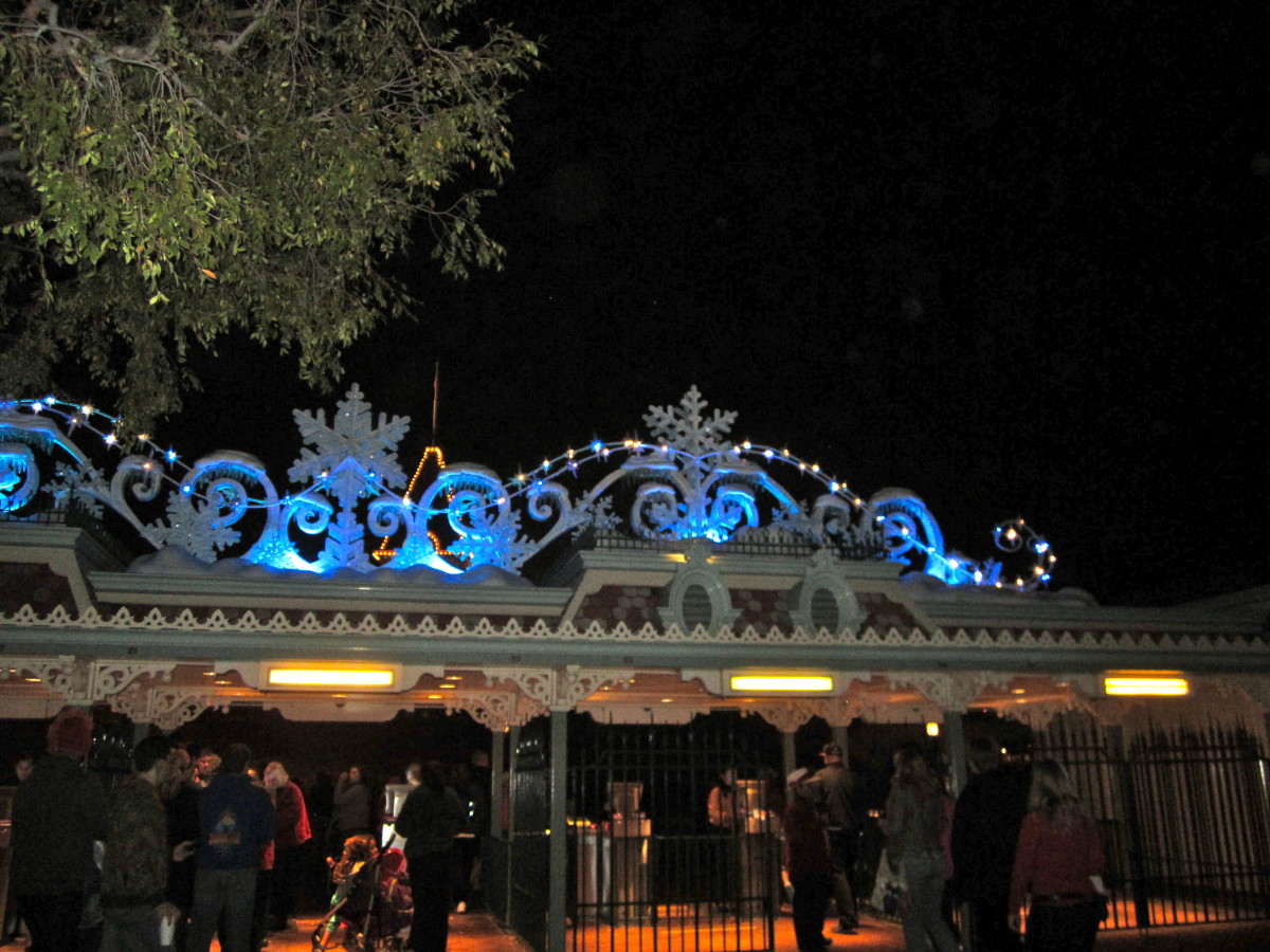 The entrance gates to Disneyland are decorated in blue light and snowflakes.
