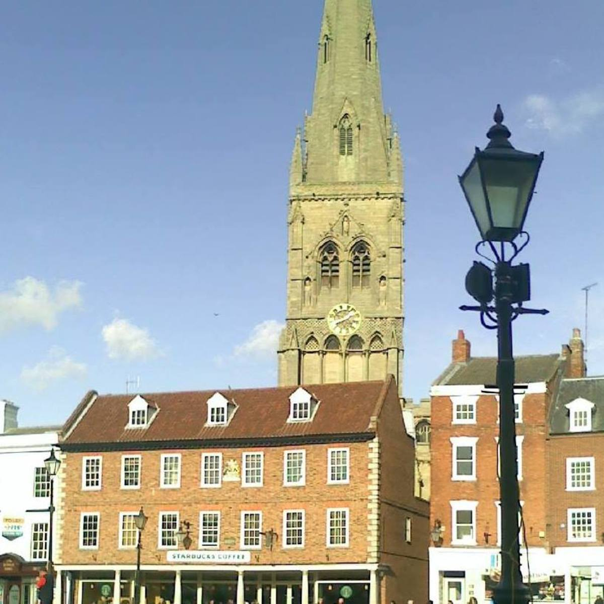 The Church of St. Mary Magdalene, locally known simply as 'the Parish Church', seen from Newark Market Place. The building centre-left is the Moot Hall.