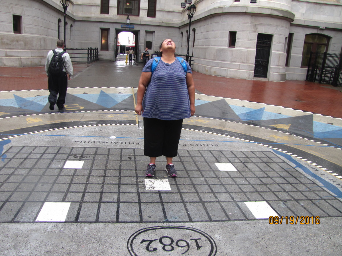 My wife standing in the courtyard of City Hall in a light drizzle.