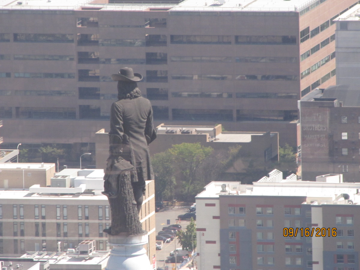 "William Penn on top of City Hall looking over his city.  ""Oh, how things have changed,"" he must be saying.  ""I'm no longer the tallest in Philadelphia.""."